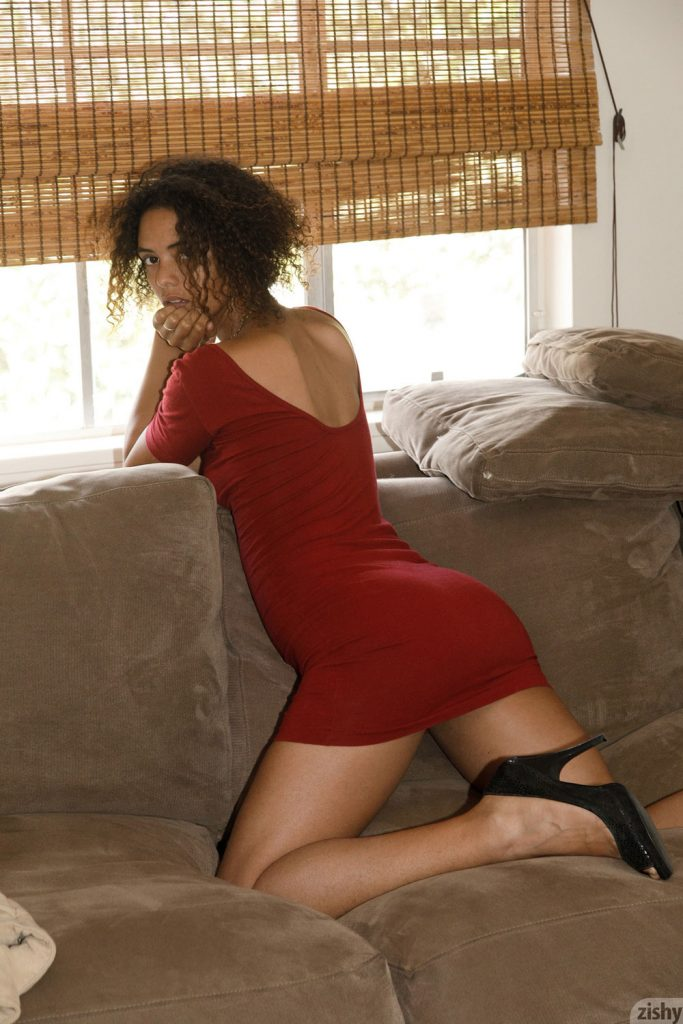 Desiree Jacobsen kneels on a chair in a tight red dress and high heels-Zishy